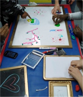 """Figure 1. Participants collaborating on frames using mixed media during """"Open Air Art"""" lesson"""